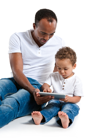Father teaching son how to use a new tablet PC. Learning and early education concept Reklamní fotografie