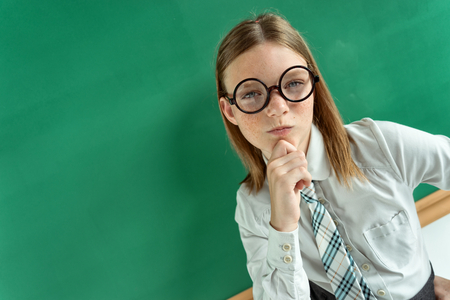skepticism: Skeptical young girl looking carefully suspicious, skepticism on face photo of teen school girl wearing glasses, creative concept with Back to school theme Stock Photo