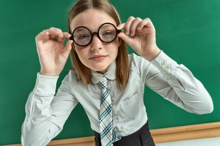 poor eyesight: Pretty suspicious scholar girl with poor eyesight gazing through her eyeglasses photo of teen school girl wearing glasses, creative concept with Back to school theme Stock Photo