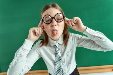 naughty child: Naughty pupil making sassy funny expressions, showing her tongue photo of teen school girl wearing glasses, creative concept with Back to school theme