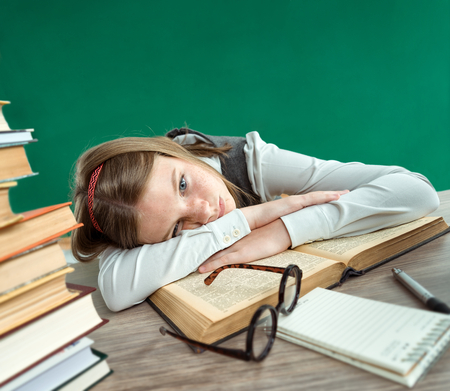 weary: Weary teen girl going to sleep at the desk lying down her head on an open book photo of teen school girl wearing glasses, creative concept with Back to school theme