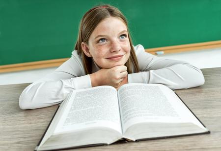 niña pensando: Fantasía alumno mirando hacia arriba como si soñando o pensando en algo agradable mientras está sentado en el escritorio con foto libro abierto de la niña de la escuela adolescente, concepto creativo con Volver a la escuela tema