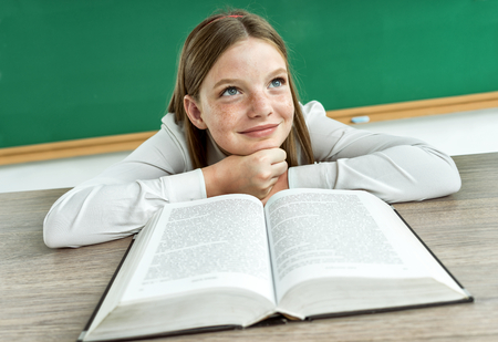 Fantasy pupil looking up as if daydreaming or thinking of something pleasant while sitting at the desk with open book photo of teen school girl, creative concept with Back to school theme Stock Photo