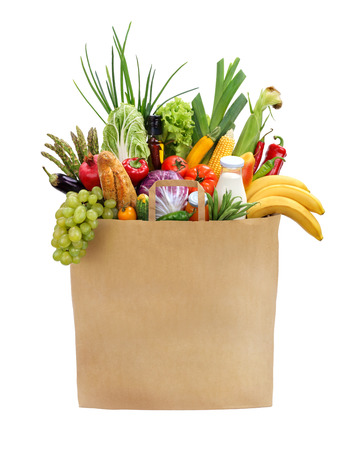 Full grocery bag studio photography of brown grocery bag with fruits, vegetables, bread, bottled beverages - isolated over white background