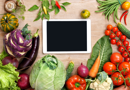 to the diet: Fresh organic vegetables on a wooden background and digital touch screen tablet. Fresh vegetables background. Diet. Dieting. Space for your text.