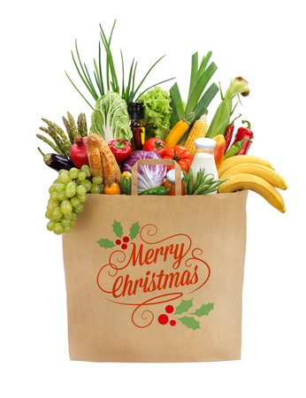 vege: Merry christmas shopping bag, studio photography of brown grocery bag with fruits, vegetables, bread, bottled beverages - isolated over white background
