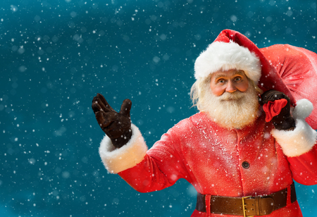 authentic: Smiling Santa Claus, carrying big bag full of gifts to children Merry Christmas New Years Eve concept Closeup on blurred blue background. Stock Photo