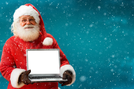 Santa Claus holding laptop Merry Christmas New Years Eve concept Closeup on blurred blue background.