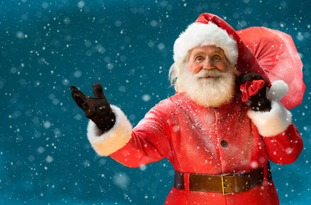 本当のサンタ クロース、ギフト、青い背景をぼかした写真の子供メリー クリスマス新年の前夜概念クローズ アップの大きなバッグを運ぶします。