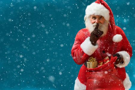 Weihnachtsmann mit großen roten Sack Zeigefinger Führung durch den Mund und auf Kamera Frohe Weihnachten Silvester Konzept Nahaufnahme auf blauem Hintergrund unscharf.