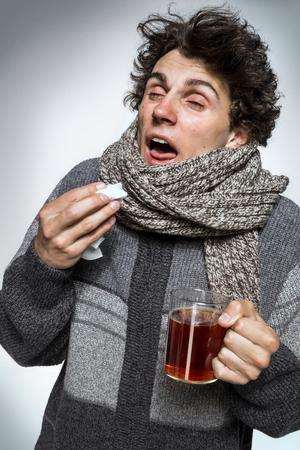 gripe: los enfermos. Gripe. hombres atrapados en frío. Estornudos en el tejido. Dolor de cabeza. Virus. medicamentos Foto de archivo