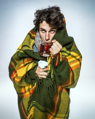 frio: Enfermedad del hombre cubierto con una manta a cuadros con té caliente enfermo que sufre virus de la gripe y el frío del invierno. Medicamentos o drogas de abuso, el concepto de salud