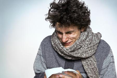 Nahaufnahmeportrait kranker junger Mann Student, Arbeiter, Mitarbeiter mit Allergien, Keime kalt, seine Nase mit Kleenex bläst, sieht sehr unglücklich unwohl, isoliert auf weißem Hintergrund. Grippe-Saison, Impfstoff Standard-Bild