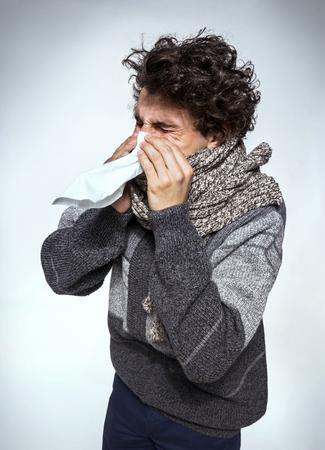 resfriado: Hombre que sostiene un tejido en su nariz contra la gripe o el fr�o - estornudos enfermos sonarse la nariz. Medicamentos o drogas de abuso, el concepto de salud