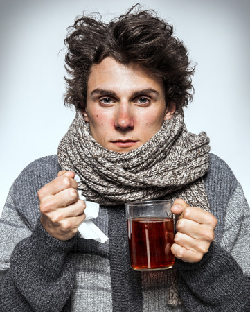 fever: Man Cold Ill young man with red nose, scarf, sneezing into handkerchief. Medication or drugs abuse, healthcare concept Stock Photo