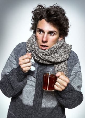 hanky: Man Cold Ill young man with red nose, scarf, sneezing into handkerchief. Medication or drugs abuse, healthcare concept Stock Photo