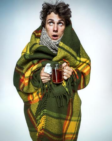 gripe: Enfermedad del hombre cubierto con una manta a cuadros con té caliente enfermo que sufre virus de la gripe y el frío del invierno. Medicamentos o drogas de abuso, el concepto de salud