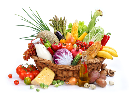 Large variety of food studio photography of wicker basket with goods on isolated white background