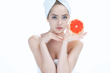 junge nackte m�dchen: Lovely girl with pomelo slice, natural organic raw fresh food concept photoset of attractive girl holding a cut piece of Sicilian orange on blue background Lizenzfreie Bilder