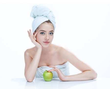 Beauty woman portrait of teen girl with clean skin Appealing woman with apple studio photography of girl holding an apple in her hand and smiling - isolated on white background