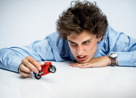Irritable office worker plays with toy motorbike photos of immature man wearing blue shirt over gray background