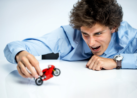 toys: Excited guy plays with red toy motorcycle photos of immature man wearing blue shirt over gray background