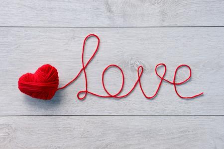 Czerwone serce czerwonej wełny przędzy na drewnianym tle. Valentines Day tle