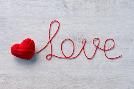 """hilo rojo: La palabra """"amor"""" escrito de hilados de lana de color rojo sobre un fondo de madera. Fondo de Valentín Foto de archivo"""