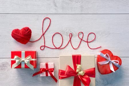 """carta de amor: Coraz�n rojo, palabra """"amor"""" y el D�a de San Valent�n cajas de regalos sobre fondo de madera. D�a de San Valent�n Foto de archivo"""