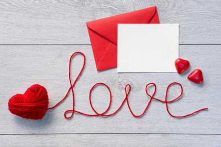 """love letter: Palabra """"amor"""" y sobre rojo con la carta en un fondo de madera. Día de San Valentín"""