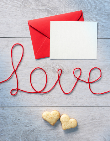 love letter: Word love, red envelope with letter and cookies on wooden background. Valentines Day background