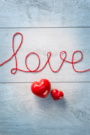 Red hearts and word love on a white wooden background. View from above. Valentines Day concept