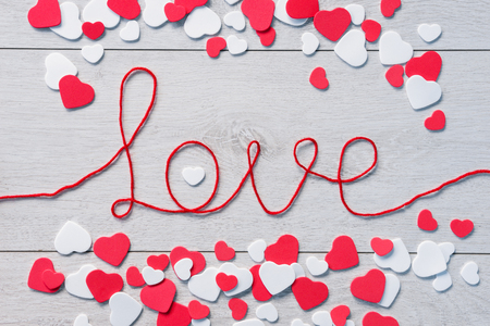 white heart: Word love with heap of small hearts on wooden background. View from above.