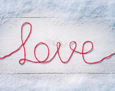 """hilo rojo: San Valentín de fondo con la nieve. Palabra """"amor"""" en el fondo de madera blanca. Fondo de Valentín Foto de archivo"""