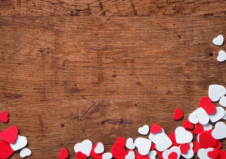 木製の背景に小さなハートのヒープとバレンタインデーの背景。 写真素材