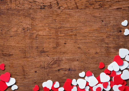 Valentines Day background with heap of small hearts on wooden background.