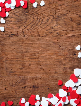 hearts background: Valentines Day background with heap of small hearts on wooden background.