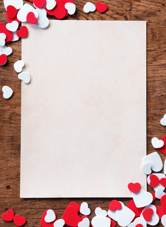 Valentines white background with heap of small hearts on wooden background.