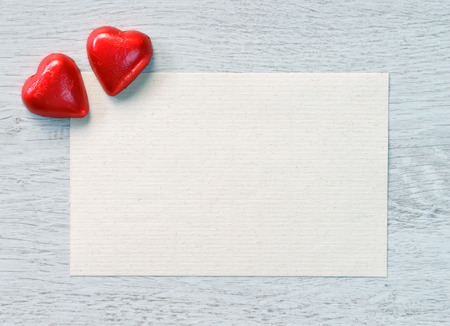 Valentinstag Bonbons und altes Papier für Glückwünsche auf einem hölzernen Hintergrund.