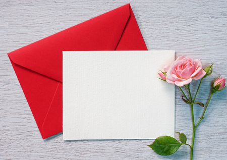 Valentine Letter and pink rose on a white wooden background.