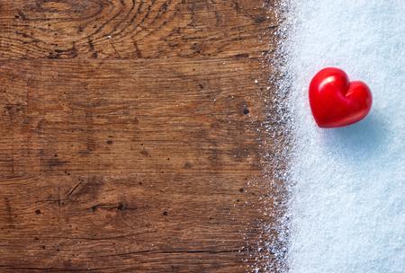 Rode steen hart op witte sneeuw winter en rustieke achtergrond.