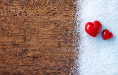 Two Red stone hearts on white snow winter and rustic background.