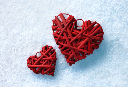 Romantic vintage red hearts together on white snow winter background.