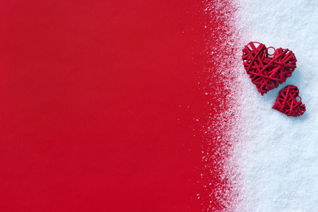 Beautiful romantic vintage red hearts on white snow winter and red background. Standard-Bild