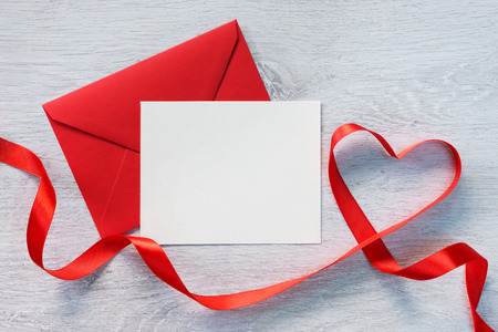 envelope: Letter and curved red ribbon on a wooden background.