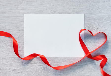 st valentin: Frame or gift card with valentines heart shaped ribbon over wooden background. Stock Photo