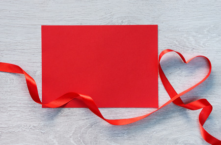 st valentin: Red gift card with valentines heart shaped ribbon over wooden background. Stock Photo