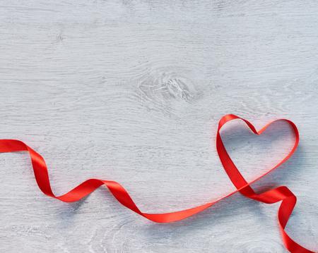 幸せなバレンタインデー。木製の背景に赤いリボンの心。