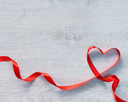 Happy Valentines Day. Red Ribbon Heart on a wooden background.