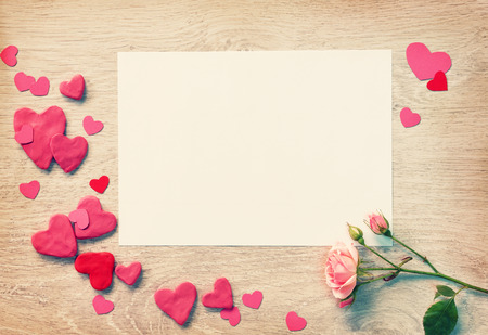 st valentin: Vintage pink card with valentines heart shaped and pink rose on a white wooden background.